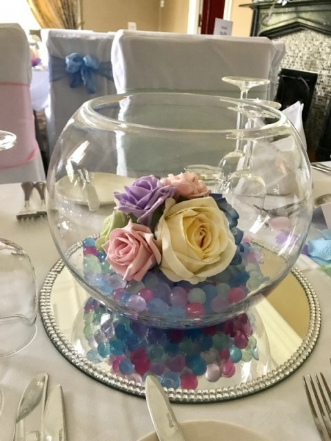 Multicoloured artificial roses in fish bowl