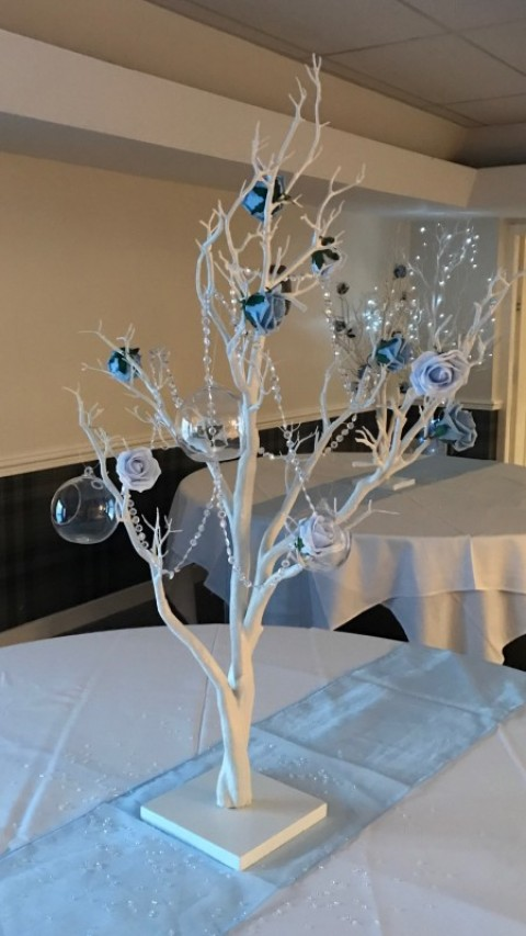 White tree decorated with pale blue roses, crystal chains and baubles. Stands over 1m