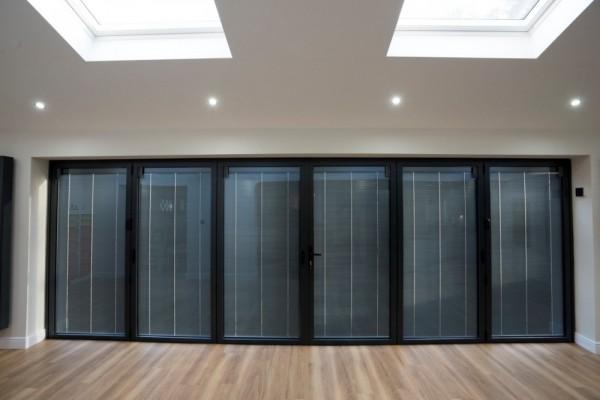 Anthracite grey aluminium bi-folding doors with integral solar power blinds