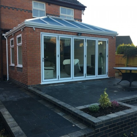 White upvc bi-folding doors with high performance glass roof