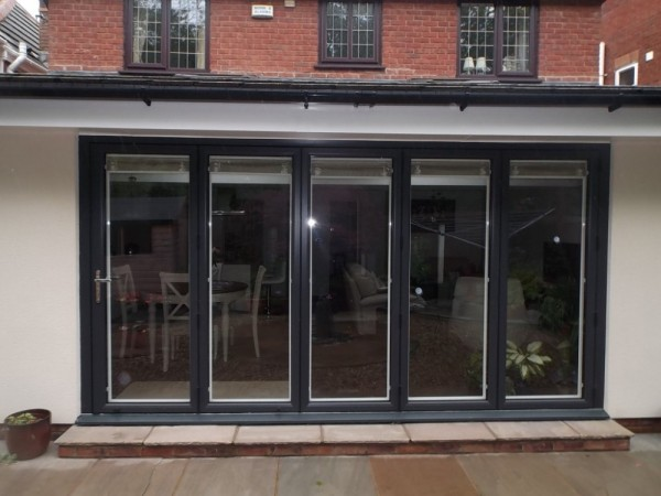Black On white UPVC Bi-Folding Doors with integral blinds