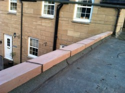This steading at Lanark Mill had received a poor quality coating to the rendered finish.  The incorrect bonding procedure had been used, allowing the de-lamination of the outer surface.  The entire coating and render was removed, properly bonded to receive a new properly bonded render coat folllowed by a Linotol coating to match the existing building.  The existing cope on the building had also encouraged water ingress by virtue of the fact it was constructed with precast slab cuts with no drip, thereby encouraging water to be drawn onto the wallhead.  A new colour matched single weathered cope was cast by Macbar with drip which effectively protected the roof edge.